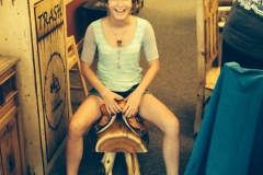Marisa sitting on our kids saddles!